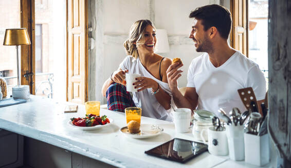 Young happy couple sitting by table in modern apartment and having breakfast together - EHF00896