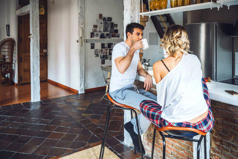 Young couple sitting at kitchen counter and having breakfast - EHF00902