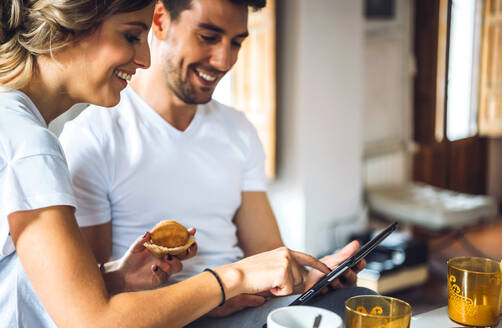 Young laughing couple having breakfast together and watching tablet while sitting by table. - EHF00905