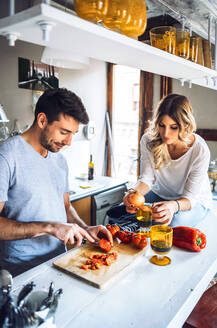 Young content couple cooking dinner and drinking wine at beautiful kitchen. - EHF00929