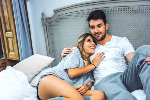 Young adorable couple sitting on bed in pajamas and embracing. - EHF00992