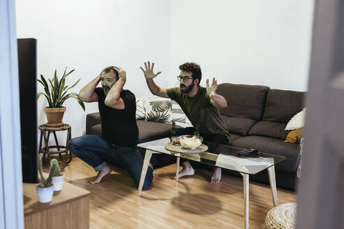 Sad male friends watching sports over TV in living room seen through doorway - XLGF00478