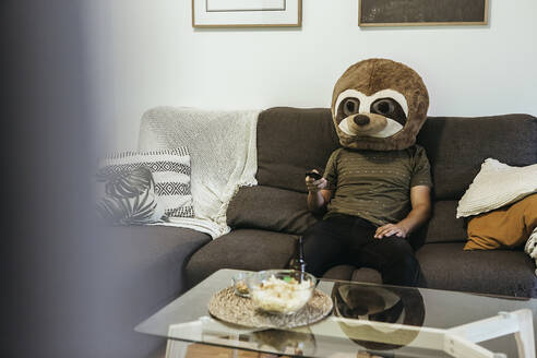 Mid adult man wearing teddy bear mask watching TV while sitting in living room - XLGF00484