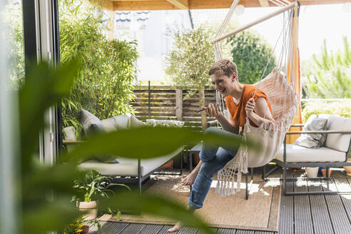 Cheerful woman talking over mobile phone while swinging in porch seen through indoors - UUF21254