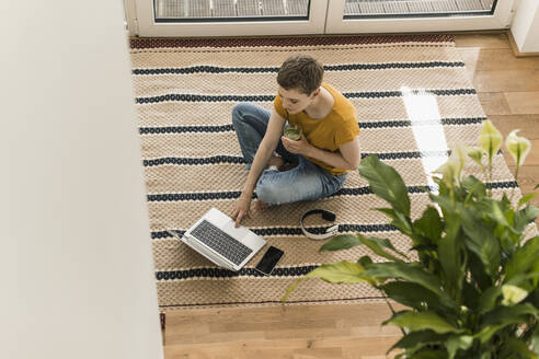 Woman with short hair holding drink while using laptop on carpet at home - UUF21317