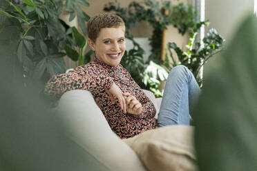 Smiling beautiful woman with short hair sitting on sofa against houseplants in living room - UUF21335