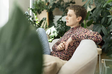Thoughtful woman with short hair sitting on sofa against houseplants in living room - UUF21338