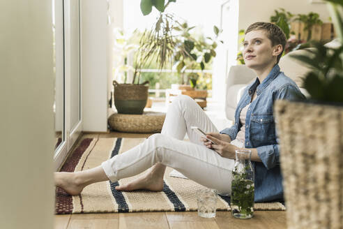 Thoughtful woman with short hair using smart phone while sitting on carpet at home - UUF21347