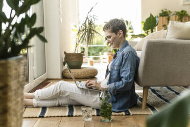 Mid adult woman with short hair using laptop while sitting on carpet at home - UUF21350