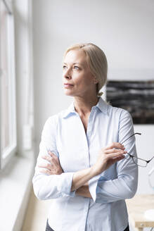 Thoughtful businesswoman with arms crossed holding eyeglasses while standing in home office - MOEF03219