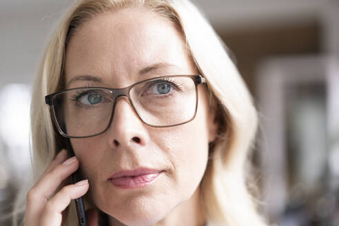 Close-up of female professional wearing eyeglasses talking over mobile phone - MOEF03249