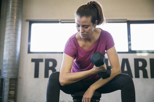 Serious female athlete lifting dumbbell while sitting in gym - ABZF03278