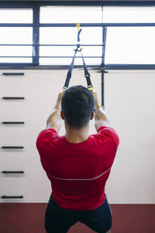 Young man pulling straps while exercising in gym - ABZF03296
