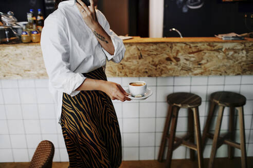 Female owner holding coffee cup while working in restaurant - OGF00530