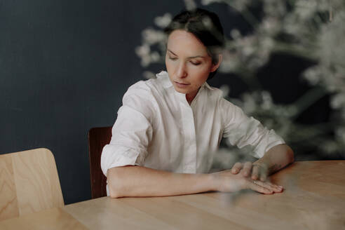 Thoughtful woman sitting at table in restaurant - OGF00545