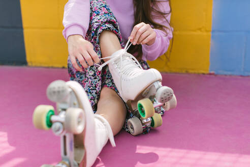 Crop young female in trendy outfit tying shoelaces on white quad roller skates while sitting on colorful playground in sunny day - ADSF15199