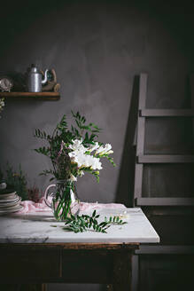 Beautiful glass vase with bunch of whites flowers with leaves on marble tabletop beside dark wall - ADSF15220