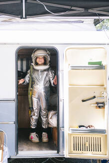 Girl wearing space suit standing in motor home seen through entrance - JCMF01360
