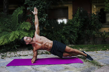 Shirtless male athlete practicing plank position on mat against plants in yard - EBBF00695