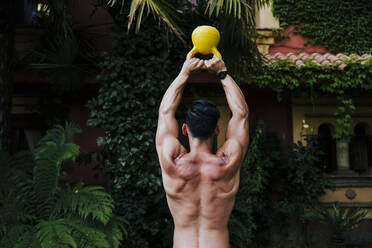 Shirtless man with arms raised lifting kettlebell while standing in yard - EBBF00713