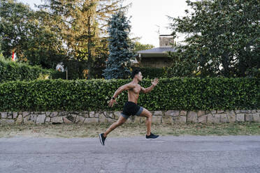 Mid adult male athlete running on road against plants in yard - EBBF00725