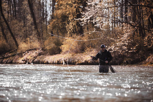 Fly Fisherman casting fishing line while standing in river at forest - DHEF00387