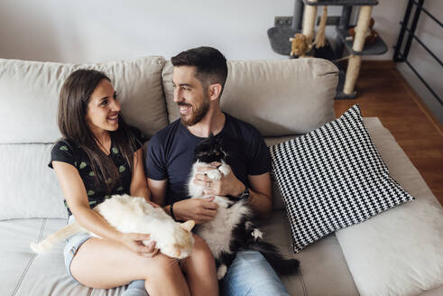 Smiling couple sitting with cats on sofa at home - SASF00060