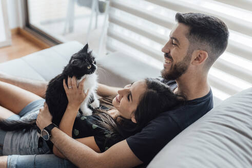 Happy couple spending leisure time with cat while sitting at home - SASF00069