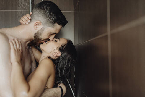 Naked romantic couple kissing each other on lips in bathroom - SASF00084