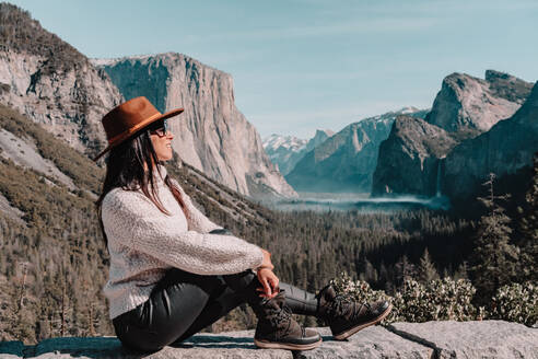 Full body side view of happy relaxed young female traveler in stylish outfit sitting on stone border against picturesque mountain scenery with rocky cliffs and coniferous forest in Yosemite National Park in USA - ADSF15247