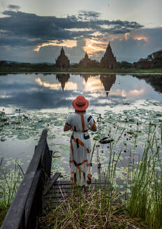 Back view of woman traveler in hat and dress standing on wooden deck at lakeside and enjoying spectacular view of temples against cloudy sunset sky reflected in calm water in Bagan Burma - ADSF15250