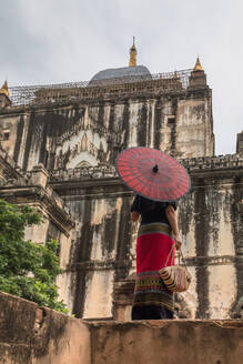 From below back view of woman in long dress holding traditional Burmese red umbrella and bag standing next to old stone building while walking and sightseeing in Bagan Myanmar - ADSF15256
