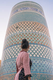 From below back view of lady in traditional clothes standing alone and looking at incomplete round tower of Kalta Minor minaret with colorful glossy brick wall on street in Khiva - ADSF15265