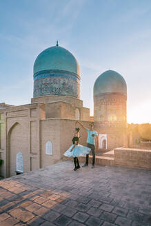Full body man and woman dancing against ancient Islamic building with domes while visiting Shah-i-Zinda in Samarkand, Uzbekistan - ADSF15274
