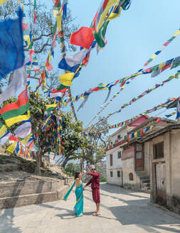 Side view of couple in casual wear walking near old Buddhist buildings under colorful garland with flags on sunny day - ADSF15277