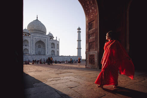 India - November 9, 2012: Indian female in traditional dress standing barefoot on square and admiring amazing view of Taj Mahal - ADSF15298