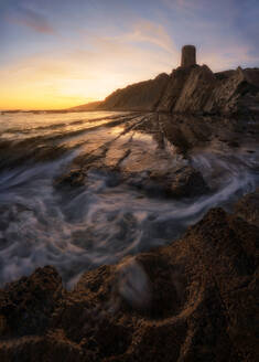 Spectacular landscape of tower on rock on background of colorful sundown in Cadiz - ADSF15304