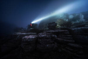 Side view of tourist standing on rocky cliff and illuminating rough boulders during foggy night - ADSF15310