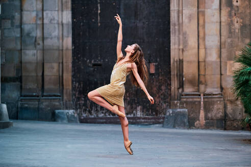 Full body of graceful young female dancer in pointe shoes performing elegant dance with arm raised on narrow paved passage against aged stone building - ADSF15328