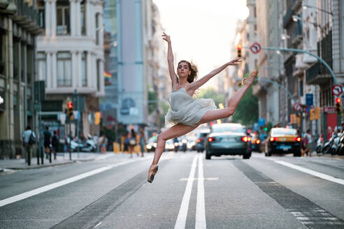 Full body side view of young slim female dancer in pointe shoes jumping and performing split over asphalt road on modern city street with cars and buildings in background - ADSF15331