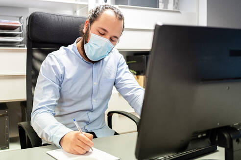 Focused young bearded male manager in formal blue shirt and protective mask making notes in notebook while sitting in chair in front of computer monitor in modern workplace - ADSF15355