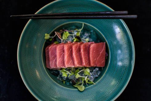 Top view of palatable raw meat slices placed on plate with ice cubes and green herbs in luxury restaurant - ADSF15385
