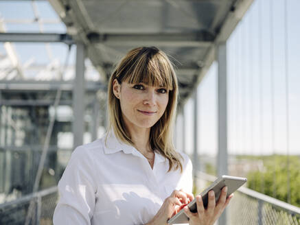Close-up of confident businesswoman using digital tablet in greenhouse - JOSEF01630