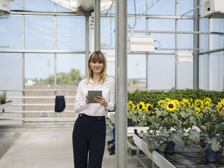 Smiling businesswoman using digital tablet while standing by plants in greenhouse - JOSEF01639