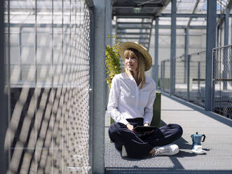 Businesswoman wearing hat using digital tablet while sitting by fence in greenhouse - JOSEF01657