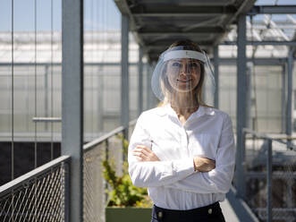 Smiling businesswoman wearing face shield with arms crossed standing in greenhouse - JOSEF01660
