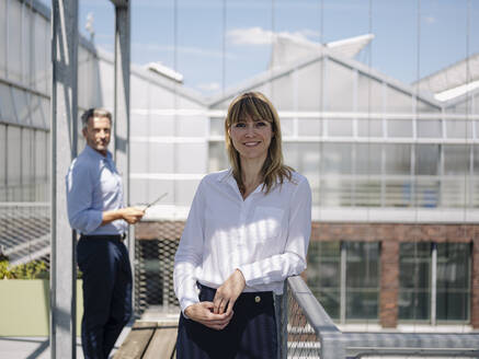 Smiling businesswoman with male coworker standing in greenhouse - JOSEF01672