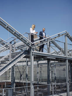 Colleagues discussing while standing on built structure against clear sky - JOSEF01681