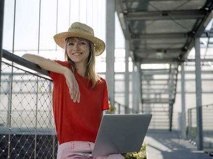 Smiling businesswoman wearing hat using laptop while sitting by railing in greenhouse - JOSEF01705