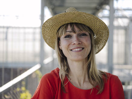 Close-up of smiling businesswoman wearing hat in greenhouse - JOSEF01708